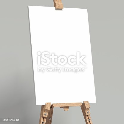 istock White easel stands next to grey wall, 3d rendering 963126718