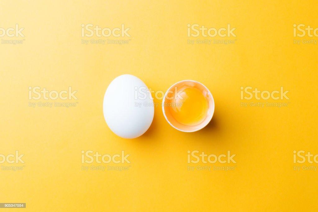 Blanco huevo y yema de huevo sobre el fondo amarillo. Topview - Foto de stock de Alimento libre de derechos
