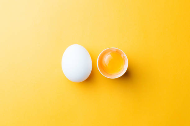 White egg and egg yolk on the yellow background. topview stock photo