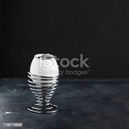 istock White egg in metal helix egg cup, opened lemonade alluminium can as top of egg on black chalkboard background with copy space, Creative concept for breakfast and Easter, Square 1133778836
