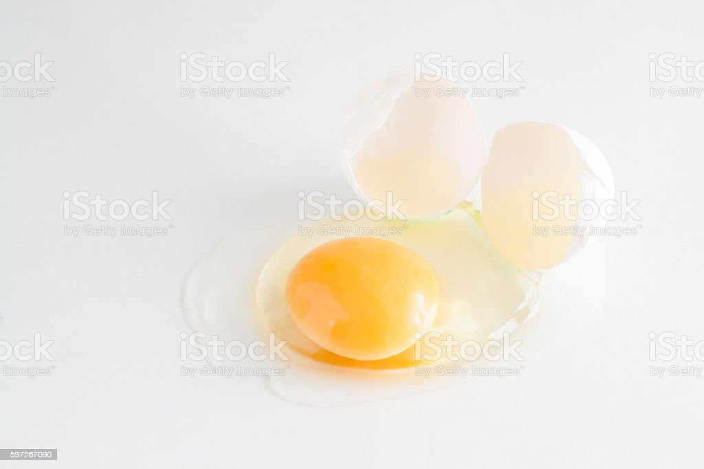 white egg is broken and leaked on a white background Lizenzfreies stock-foto