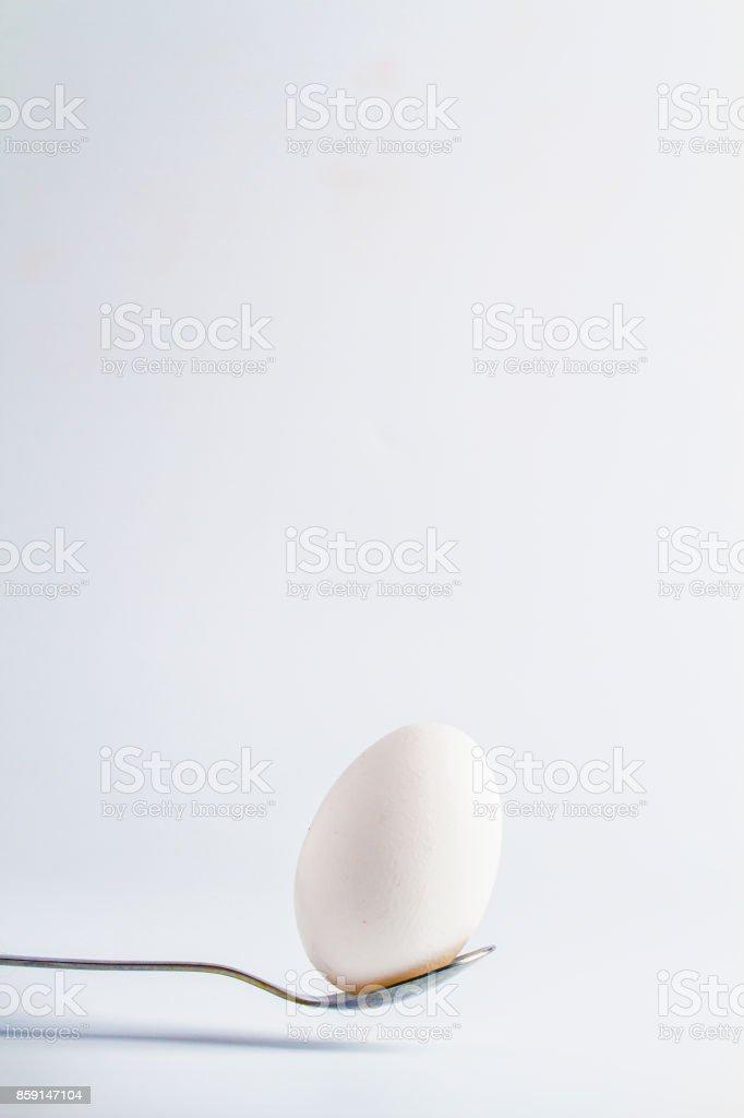 white egg on a spoon stock photo