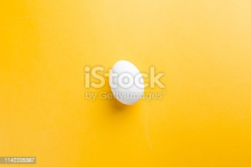 White egg on the yellow background in center. Pop art design minimalism style