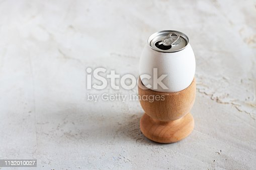 istock White egg with opened alluminium can in wooden egg cup on grey cement textured background, Horizontal banner, Copy space, Breakfast, Creative, Concept, Minimal, Easter, Lemonade, Fizzing 1132010027
