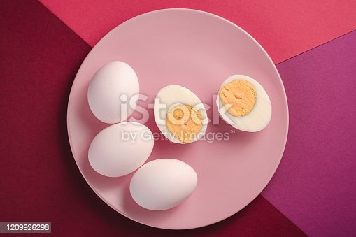 White egg with peeled boiled eggs in pink plate on purple, pink and red colors plain minimal background, top view, happy Easter day