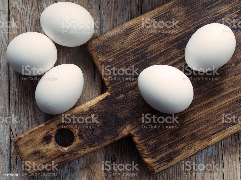 White eggs and a cutting board on a wooden table. stock photo
