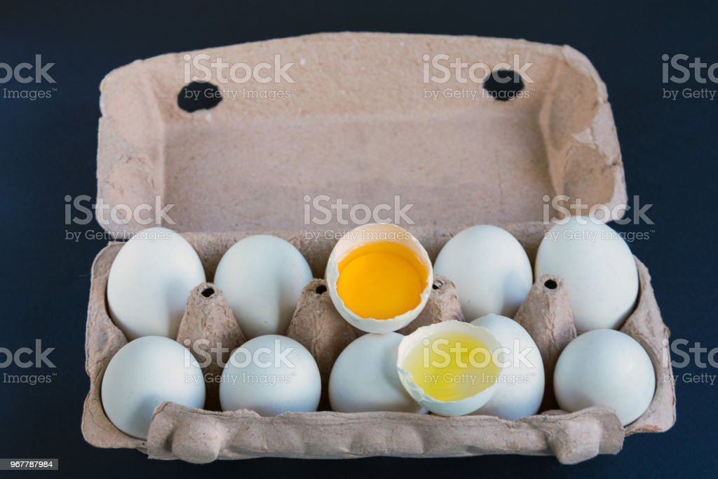 White Eggs And One Broken Egg In The Carton Box With Mockup To