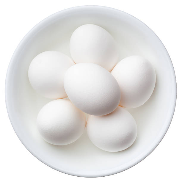 White eggs in a bowl isolated on white stock photo