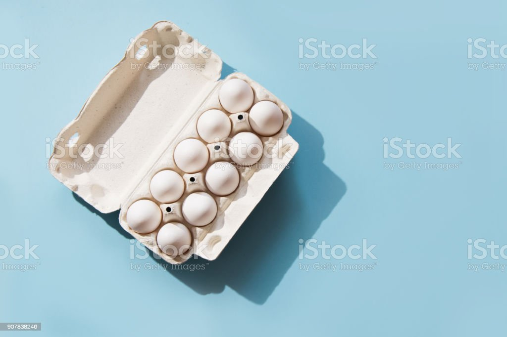 White eggs in the package on blue. Top view. stock photo