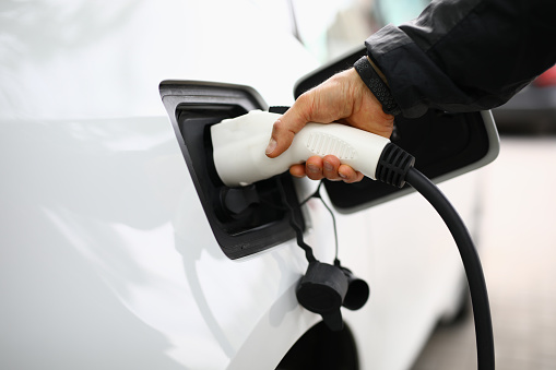 Male hand insert electric white gun into car. White electric car be recharged at charging station.