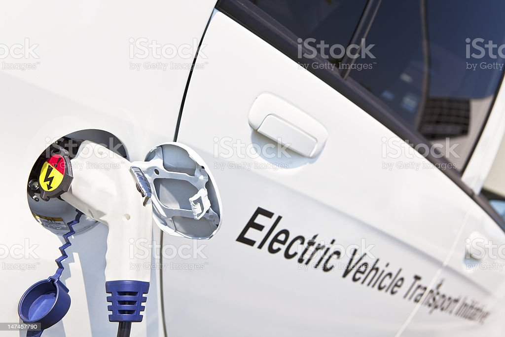 White Electric Car is being charged Outdoor royalty-free stock photo
