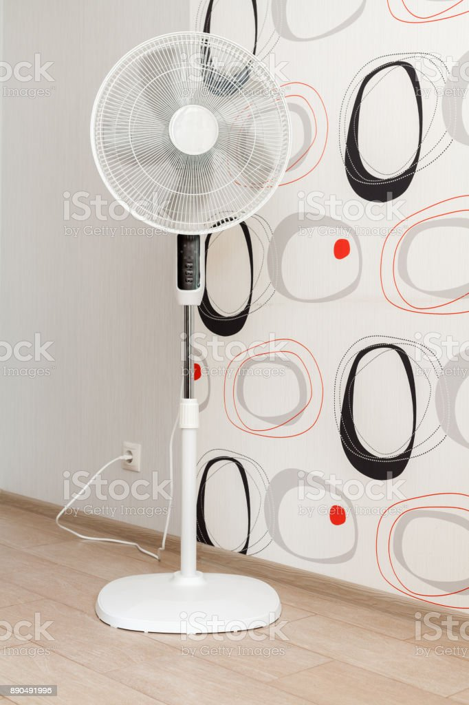 A white electric fan stands in a spacious room and cools the air stock photo