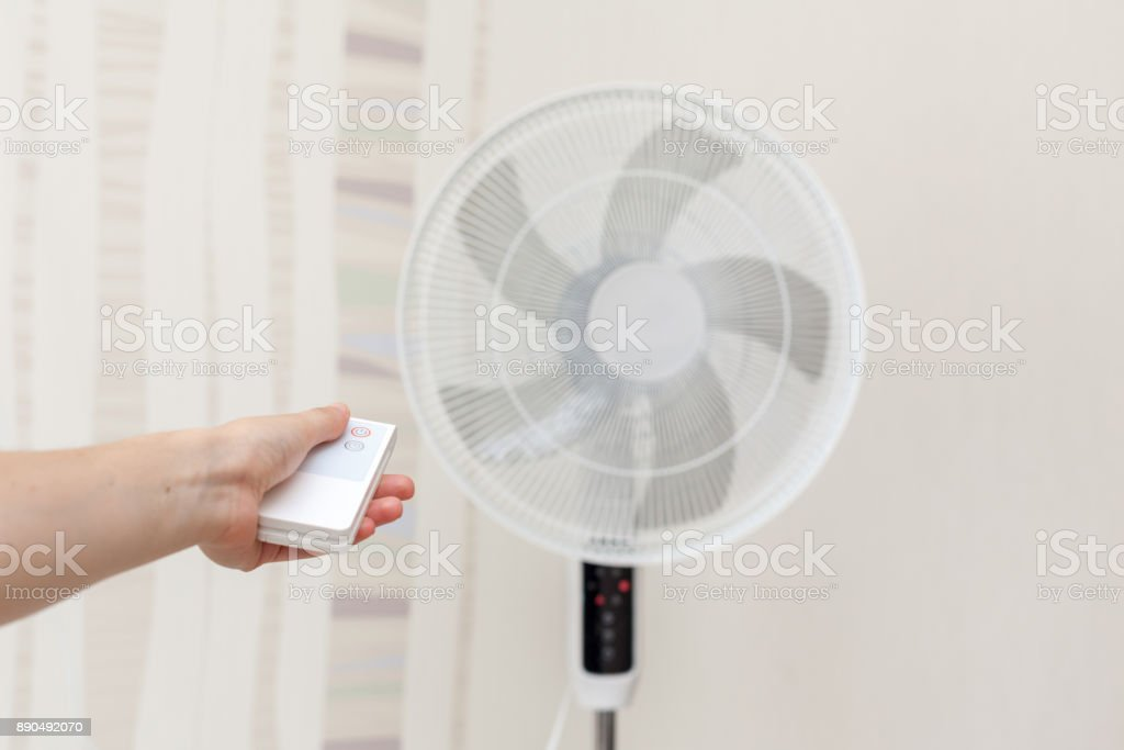 White electric fan turns on, turns off with the remote control. Hand hold electric fan remote. stock photo