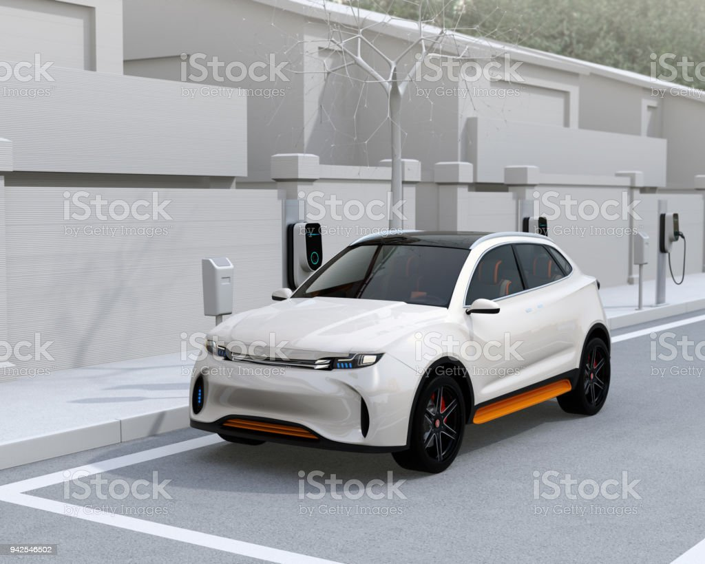White electric SUV charging at parking lot with charging station in the street stock photo