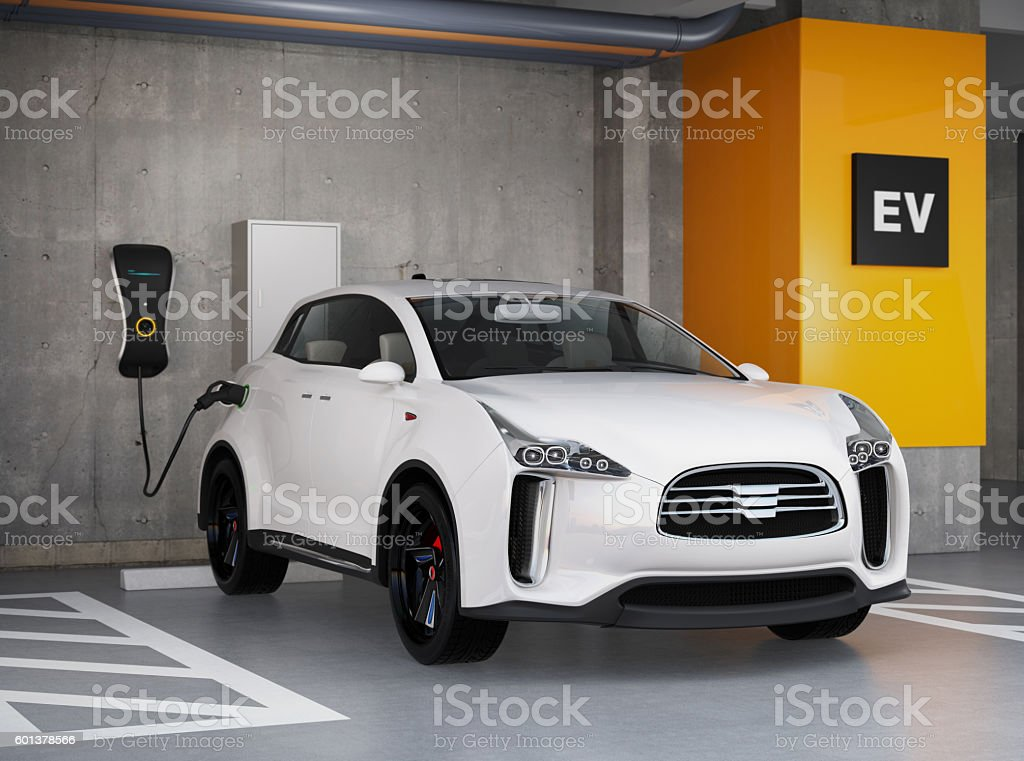 White electric SUV recharging in parking garage stock photo