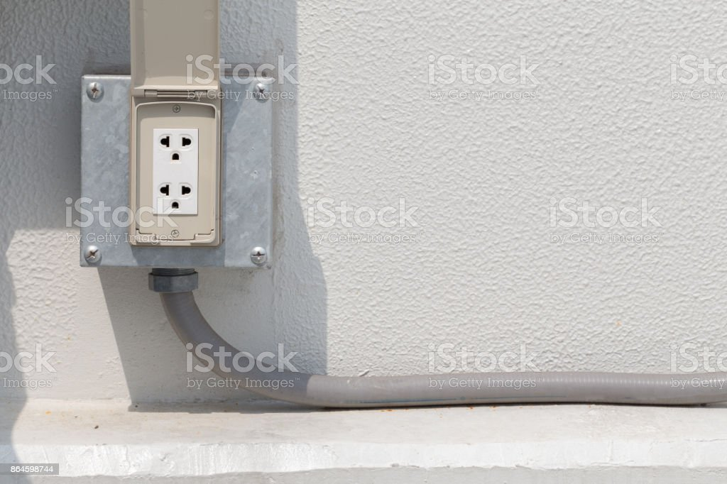 white electrical outlet or plug housing with waterproof cover at outdoor stock photo