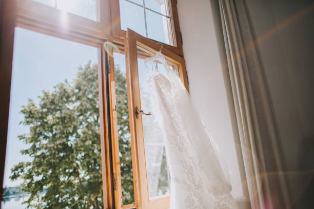 White elegant fashionable bride dress hanging in bright room stock photo