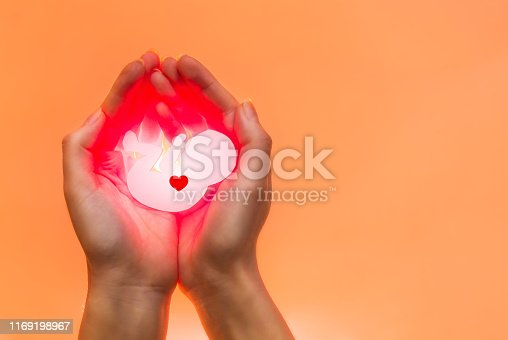 istock White embryo from paper with red heart and red light rest in hands of African-American or Asian woman. Hands on the left side. Soft focus. Orange background with the light from below. 1169198967