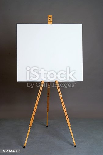 istock White empty artistic canvas on an easel for drawing images by an artist on a gray background in the studio. Background 823433772