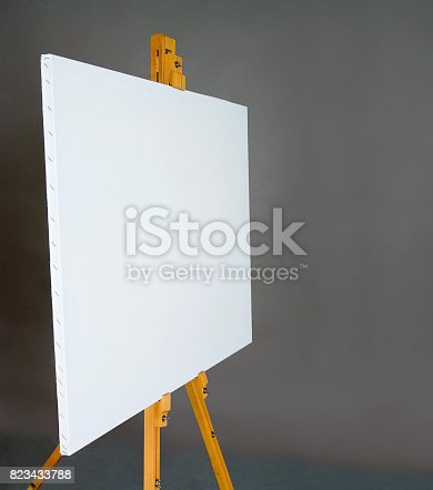 istock White empty artistic canvas on an easel for drawing images by an artist on a gray background in the studio. Background 823433788