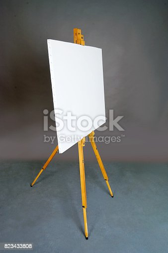 istock White empty artistic canvas on an easel for drawing images by an artist on a gray background in the studio. Background 823433808