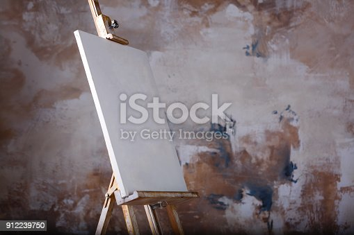 671393252istockphoto White empty artistic canvas on an easel for drawing images by an artist on a gray background 912239750