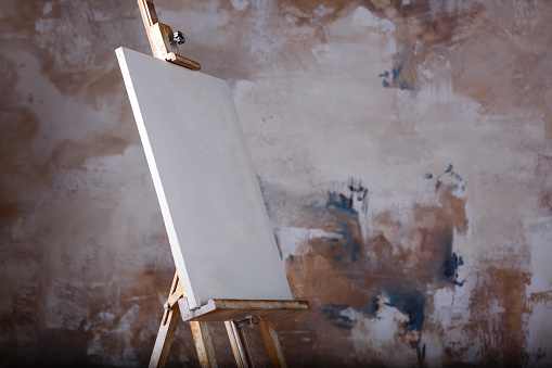 istock White empty artistic canvas on an easel for drawing images by an artist on a gray background 912239750