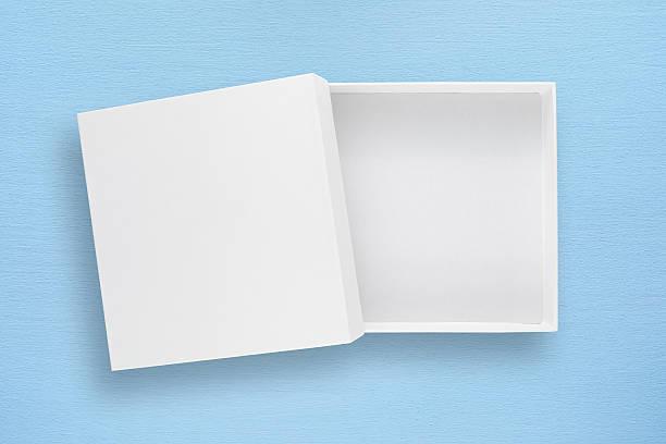 white empty cardboard box with cover on blue table - puste pudełko zdjęcia i obrazy z banku zdjęć