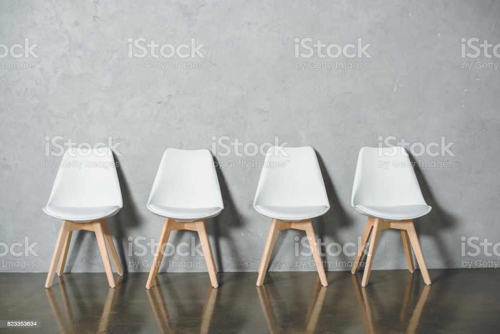 white empty chairs for job interview standing in line in hall stock photo