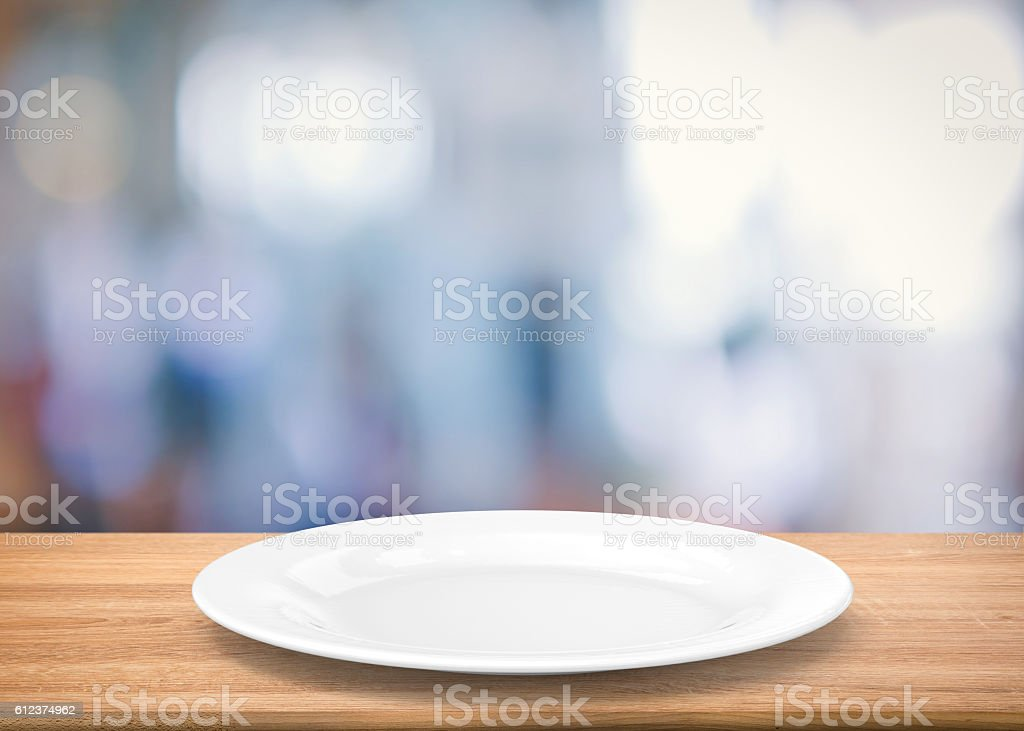 white empty dish on wooden table stock photo