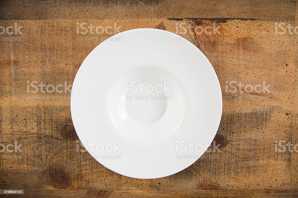 Close up of white empty plate at the wooden table with copy space