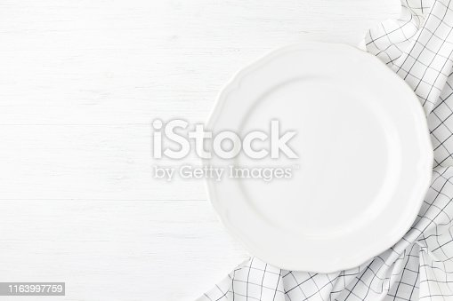 White empty plate on checked napkin on white wooden table. Blank dish top view.