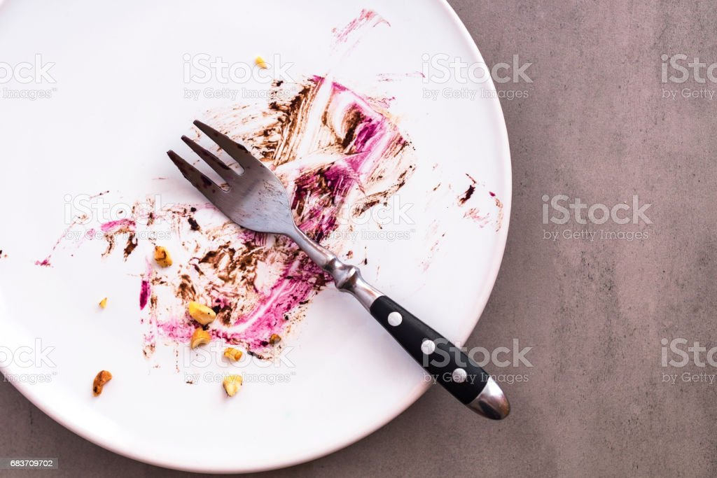 White empty plate with piece of cake leftovers stock photo
