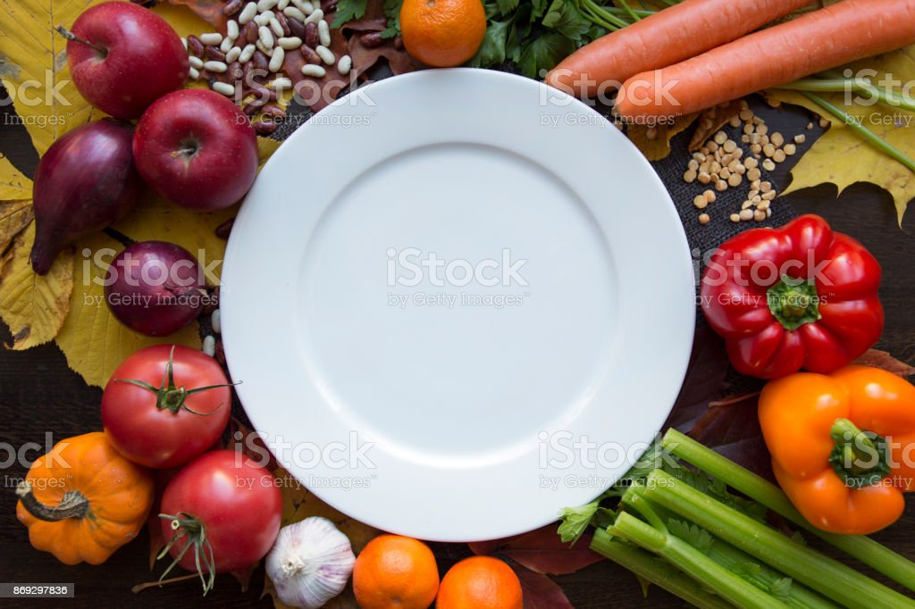 White empty plate with various vegetables top view stock photo