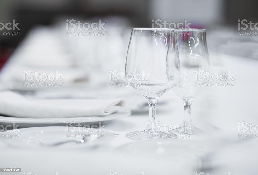 Weiße leere Teller und Gläser auf einem Tisch für eine Feier serviert - Lizenzfrei Essgeschirr Stock-Foto