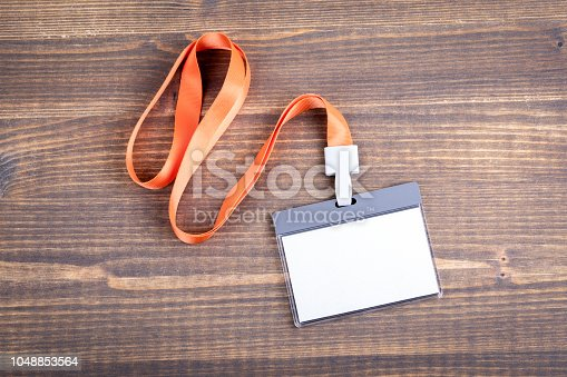 1049305186istockphoto White empty staff identity mockup with orange lanyard. Name tag, ID card 1048853564
