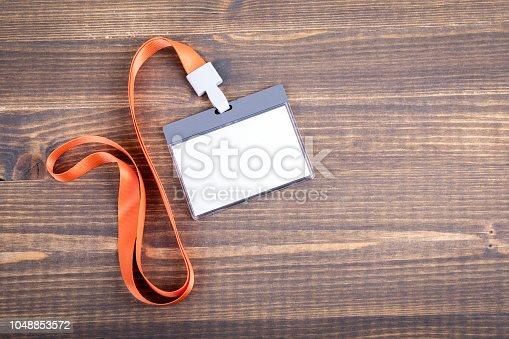 1049305186istockphoto White empty staff identity mockup with orange lanyard. Name tag, ID card 1048853572