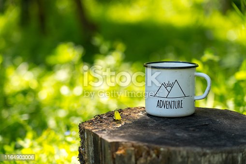 white enamel cup with mountains drawing and adventure text on aged stump in wild forest