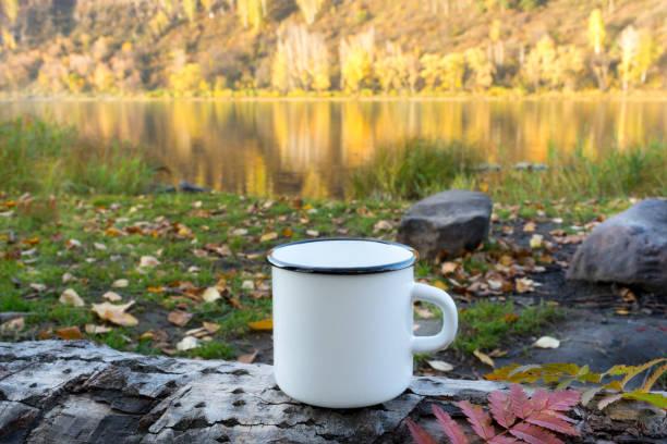 White enamel mug mockup with red leaf stock photo