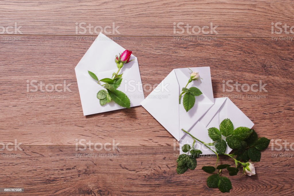 White envelope and a white and red rose. Greeting card. Conceptual photography. Wedding invitation card. Valentine day. Flat lay, top view, copyspace foto de stock royalty-free