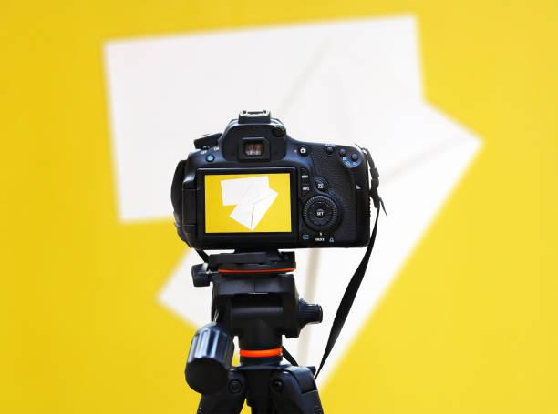 weißer umschlag isoliert auf gelbem hintergrund - nachrichten video stock-fotos und bilder