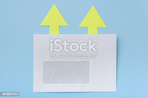 istock White envelope with arrows in one direction, blue background 943307514