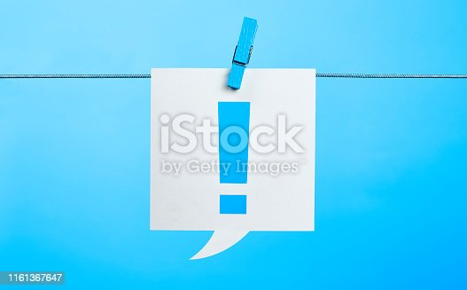 White Exclamation Point Chat Bubble Hanging On Blue Background With the Latch