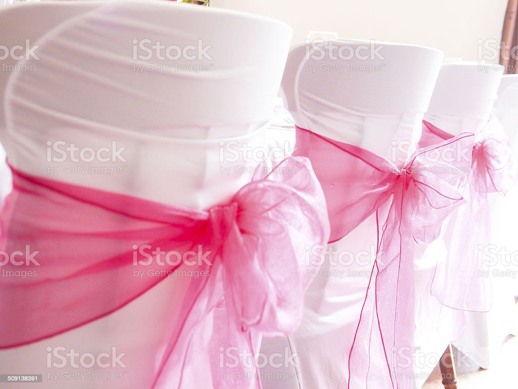 White Fabric Chair Covers with Pink Sash stock photo