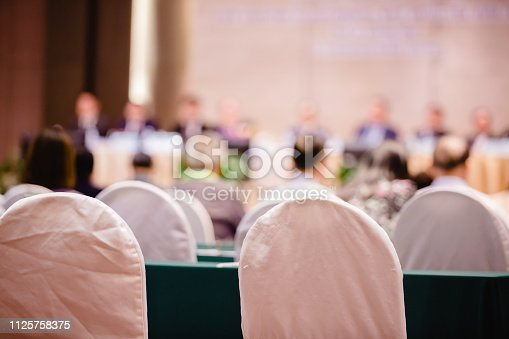 White fabric chair with blurry of auditorium for shareholders' meeting or seminar event.