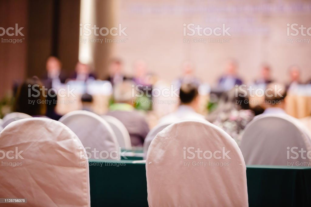 White fabric chair with blurry of auditorium for shareholders' meeting stock photo
