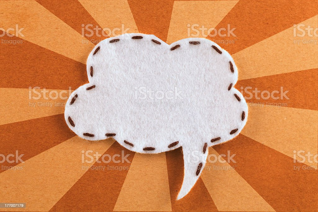 A white fabric speech bubble on brown and beige fabric royalty-free stock photo