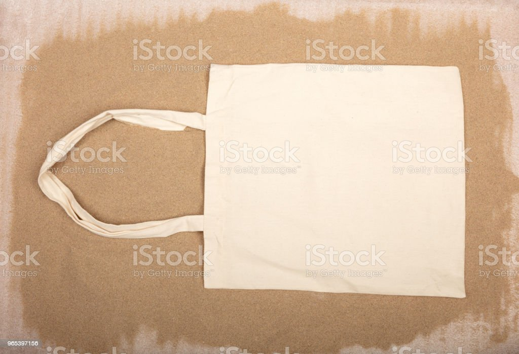 White fabric tote bag on sandy  background. royalty-free stock photo