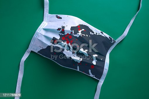 istock White face mask with a map of Europe is lying on a green background 1211788629