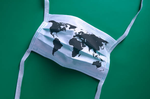 white face mask with a map of the world is lying on a green background - covid stock pictures, royalty-free photos & images